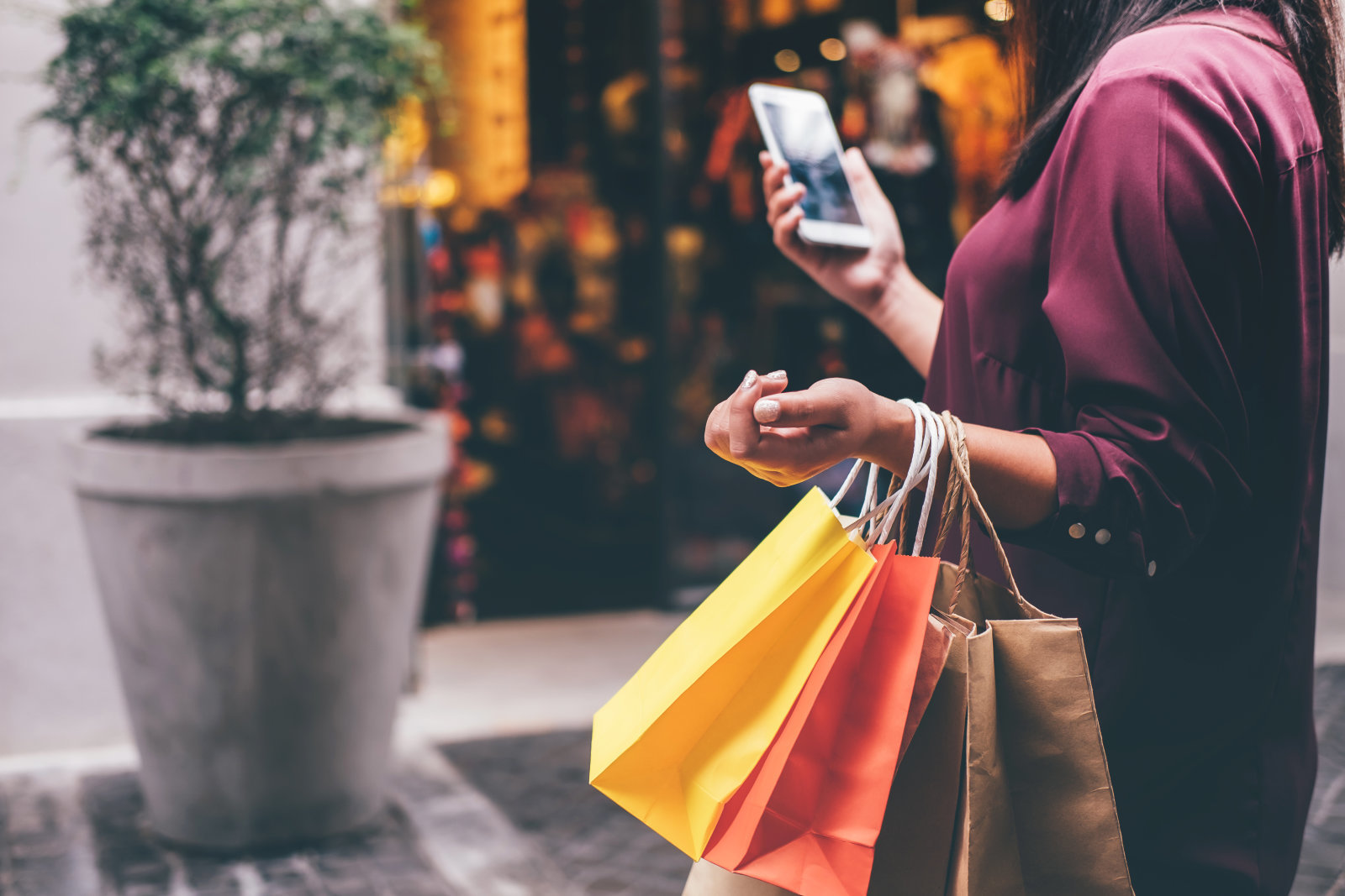 Consumerism, shopping, lifestyle concept, Young woman holding colorful shopping bags and smartphone enjoying in shopping.